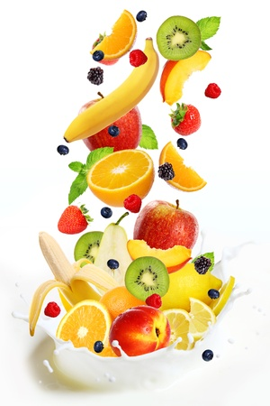 Different fresh fruits falling into splash of milk