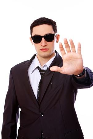 agent de s�curit�: Serious Man en costume montre un panneau d'arr�t isol� sur fond blanc