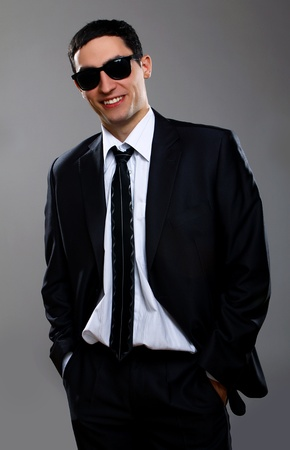 Young and attractive businessman in sunglasses over gray background photo