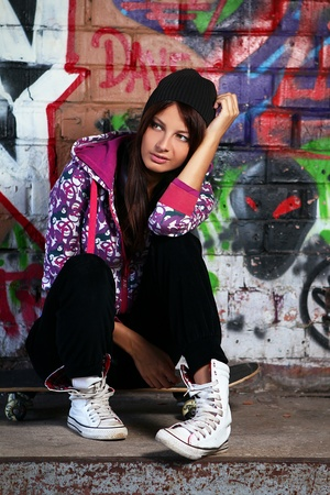 Young and beautiful girl sitting on skateboard against wall with graffiti photo