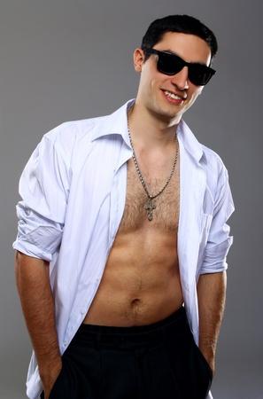Stylish guy in sunglasses over gray background photo