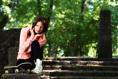 Beautiful teenage girl with headphones and skateboard in the park photo