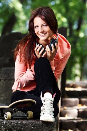 girl headphones: Beautiful teenage girl with headphones and skateboard in the park