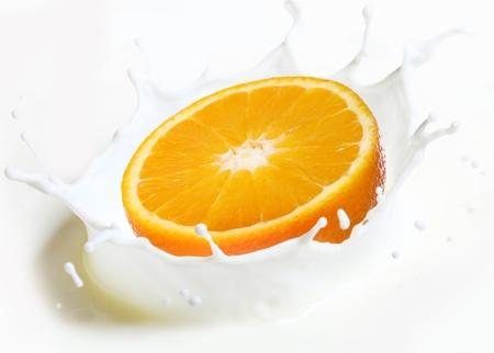Orange falling into a splash of milk photo