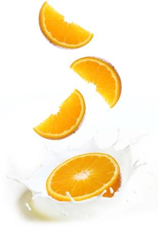 Splashes of milk with slices of fresh orange fruit photo
