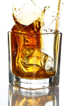 Glass with splashes of whiskey against white background photo