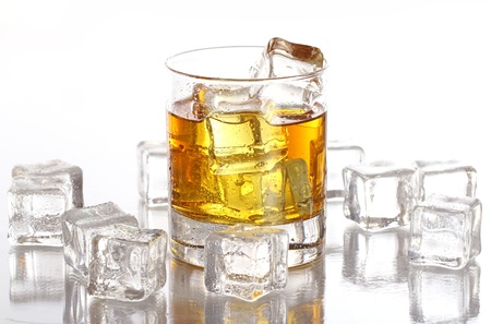 hard liquor: Glass of cold whiskey with ice isolated over white Stock Photo
