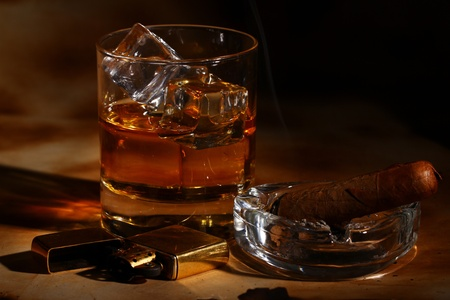 Cold whiskey  and cigar against ancient background photo