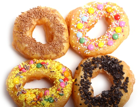 Tasty colorful donuts against white background photo