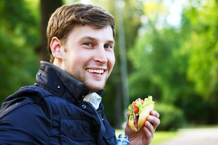 adult sandwich: Young and attractive man relaxes in the park at lunch time Stock Photo