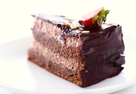fudge: Slice of tasty chocolate cake with strawberry on top against white background