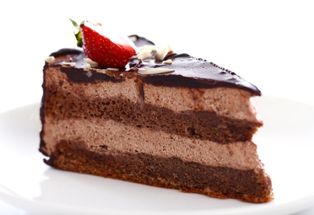 Slice of tasty chocolate cake with strawberry on top against white background photo
