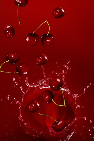 Cherry falling into the juice with huge splashes photo