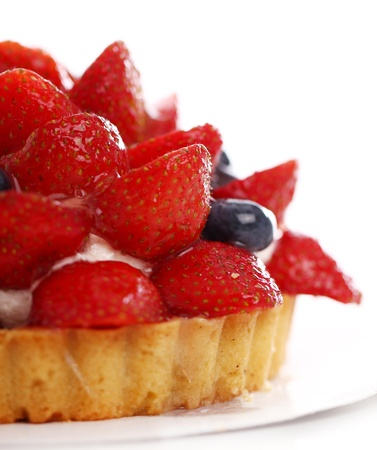 Fresh and tasty cake with strawberry and blueberry against white background photo