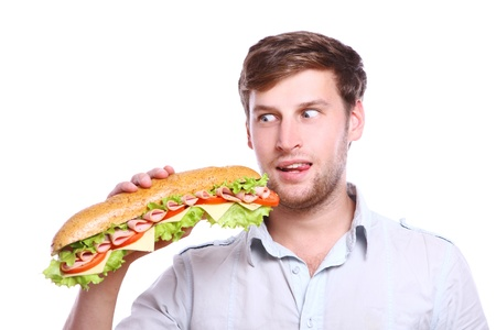 hombre comiendo: Joven con gran s�ndwich aislada sobre fondo blanco