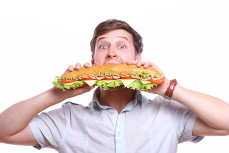 Young man with big sandwich isolated over white background photo