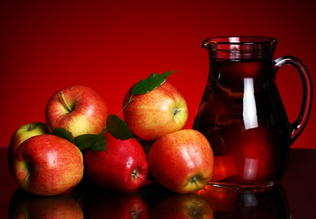 Apples and pitcher with juice against red background photo