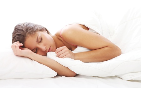 bedding indoors: Young and Beautiful woman sleeping in bed