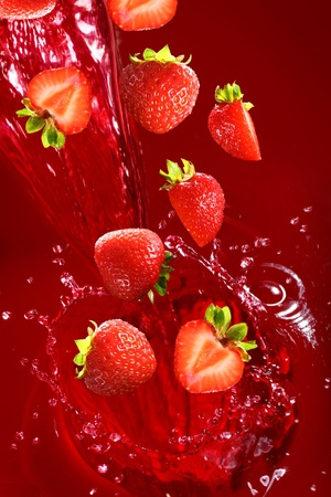 Strawberry falling into the juice with huge splashes photo