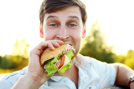 adult sandwich: Young man eating sandwich in the park