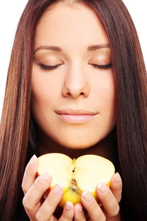 Beautiful woman with apple in hands against white background