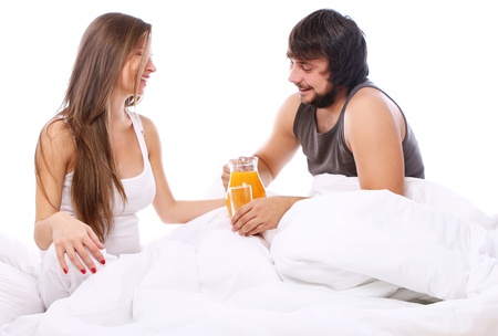 Young couple drinking orange juice in bed photo