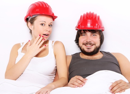 safe sex: Young and happy couple with hard hats on heads in bed. Safe sex concept. Stock Photo