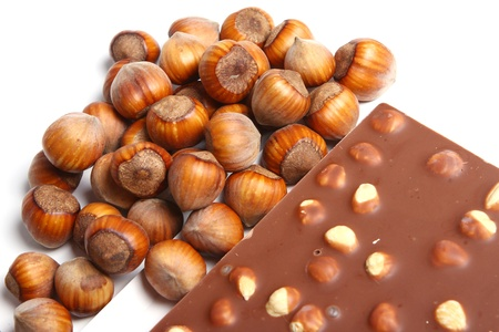 Close up of tasty chocolate with hazelnuts against white background photo