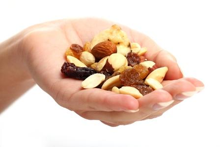 frutas secas: Mano con diferentes frutas secas sobre fondo blanco