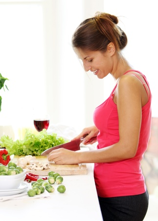 Young and beautiful woman cooking healthly food photo