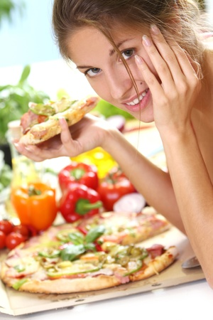Beautiful woman with pizza on the kitchen photo