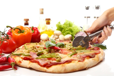 Slicing fresh pizza with pepperoni and vegetables