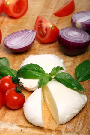 Fresh and tasty tomatoes, basil and mozzarella on wooden board photo