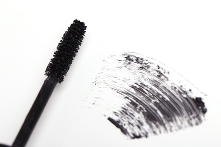 Brush of black mascara for eyes against white background photo