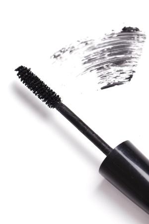 Brush of black mascara for eyes against white background photo