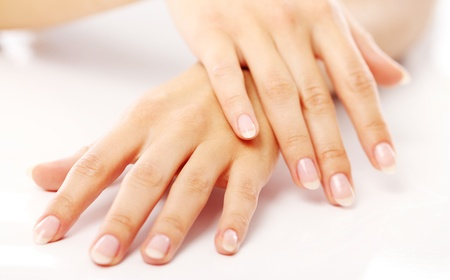 Beautiful hands with french manicure against white background photo
