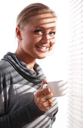 Beautiful woman in gray pullover with cup of coffee beside a window photo