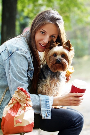 Beautiful woman have lunch while strolling with her dog in the park Stock Photo