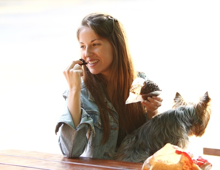 Beautiful woman have lunch while strolling with her dog in the park Imagens