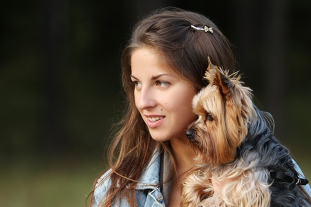 Beautiful woman with her cute dog in the park photo