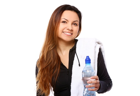 Beautiful smiling woman with  bottle of water and towel isolated over white photo