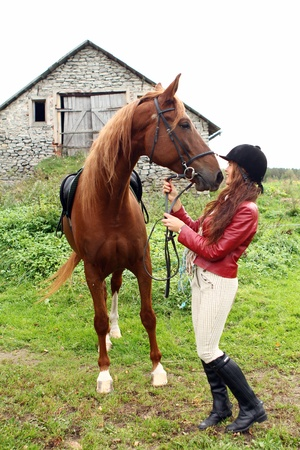stable: Woman and her beautiful  brown horse