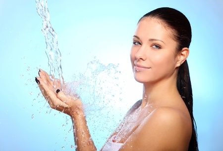 Beautiful woman under splash of water against blue background Stock Photo - 11209538