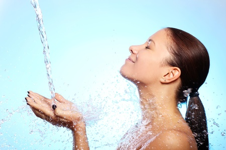 Beautiful woman under splash of water against blue background Stock Photo - 11209547