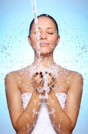 Beautiful woman under splash of water against blue background photo