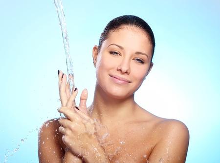 Beautiful woman under splash of water against blue background photo