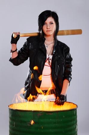 Punk girl holding baseball bat beside a barrel with burining fire inside photo
