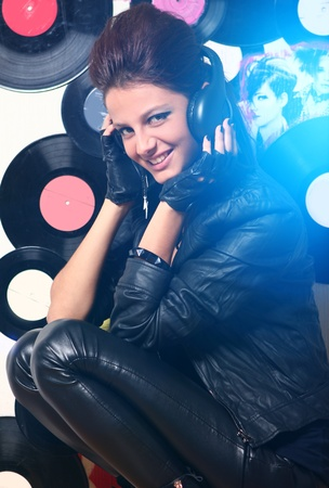 Beautiful girl with headphones in blue highlight against wall with vinyls photo