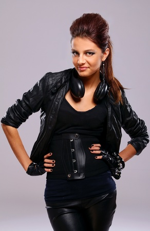 Beautiful girl in leather with headphones over gray background photo