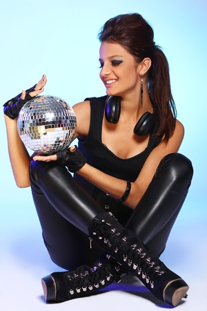 Beautiful girl with headphones and disco ball over light blue background Stock Photo - 11209646